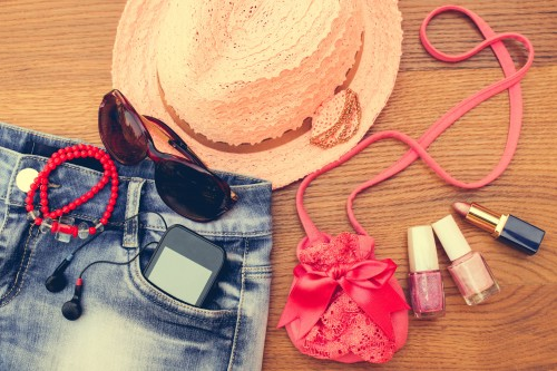 Summer women's accessories: sunglasses, beads, denim shorts, mobile phone, headphones, a sun hat, handbag, lipstick, nail polish. Toned image