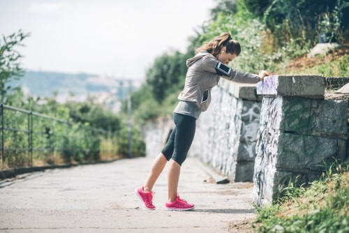 Woman runner stretching against rock wall
